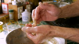 Close up of a man making matzah balls or meat balls with his hands covered in oil before he places it in a pot for cooking.