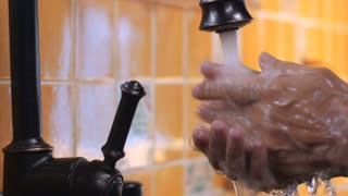 Close up of a man's hands turning off a faucet after washing his hands in slow motion