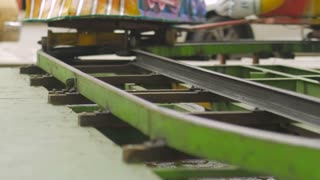 Close up of a vintage kiddie train carnival ride on metal tracks in slow motion with sparks