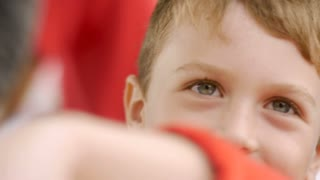 Close up of a young boy's eyes looking at the camera with his arm in front of his mouth - slowmo