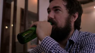 Close up of a young hipster man with a full beard drinking a beer at a bar and then laughing at someone telling him a good joke. He slaps his knee and laughs very hard.