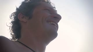 Close up of an attractive man with sun glare standing in the ocean having a good time, laughing and smiling