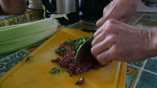 Close up of food and then pull out to reveal an elderly man chopping fresh parsley with raw liver of a cutting board with a knife by hand in his kitchen.