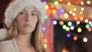 Close up portrait of a beautiful, attractive, young woman wearing a Santa hat in front of a fireplace and colored Christmas lights