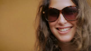 Close up portrait of a young attractive woman with long brown hair and freckles smiling for the camera as she takes off her sunglasses