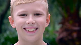 Close up portrait of a young blond boy approximately 8, 9, or 10 years old, smiling outside with shallow depth of field