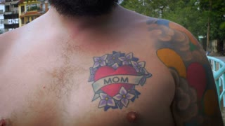 Close up portrait of a young hipster man with a full beard, bare chest, and a mom tattoo and full sleeve arm tattoos that are released for use.