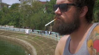 Close up portrait of a young hipster man with a full beard lighting a cigarette and smoking outside wearing a tank top next to a lake on a warm summer day.