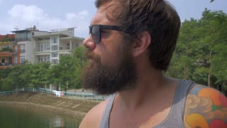 Close up portrait of a young hipster man with a full beard, sunglasses, and tattoos, smoking a cigarette and drinking a beer outside. An example of an unhealthy lifestyle.