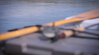 Close up rack focus of a single fly fishing rod resting in a canoe with a wooden paddle on a river during a fishing trip.