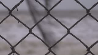 Close up shallow depth of field of rough seas through a chain link fence during a storm with large waves representing climate change.