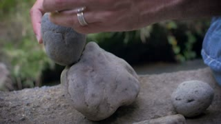 Closeup 4k footage of a man balancing rocks outdoors in nature choosing the exact spot on each spot.
