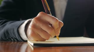 Closeup of business man writing in notebook with pen while sitting at a desk during daylight hours. Office or home office.