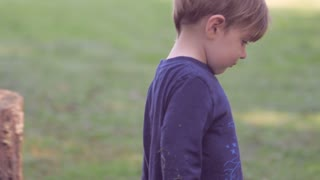 Cute little blond boy in blue clothes walks and plays on green grass turns to look at the camera in slow motion with soft focus and soft natural lighting.