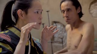 Dolly shot of a Japanese woman screaming with her hands on her face while a man without a shirt reacts because her yelling is hurting his ears. Both are performing a modern dance routine.