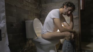Dolly shot of a man sitting on a toilet feeling ill, depressed, or upset. He could be groggy, hung over, tired, or sick. Shot with dramatic professional lighting.