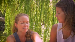 Dolly shot of two young attractive girlfriends talking to one another in an intimate and personal serious conversation while sitting outside under a tree by a water pond on a bright summer day.