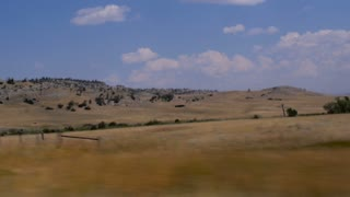 Driving along central Montana showing hills with pine trees and grass in slow motion