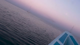 Dutch angle of the bow of a boat moving across the ocean or lake towards a sailboat during sunrise or sunset