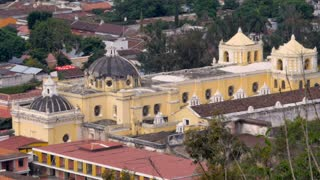 Establishing shot of a large yellow church shot from above in Antigua, Guatemala. You can see some of the repairs that have been done to the main dome