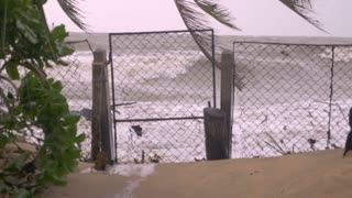 Fast shutter speed of ocean waves crashing through a closed gate during a storm representing rising sea levels, global warming, or climate change.