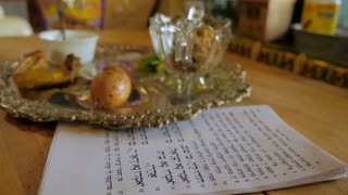 Fly over of a typical passover seder plate and Haggadah