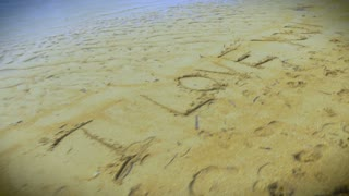 "Fly over shot of the words ""I Love You"" hand written in the sand on the beach."