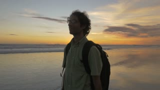 Front view of a middle aged man with glasses and a big nose enjoying the ocean sunset view in Bali