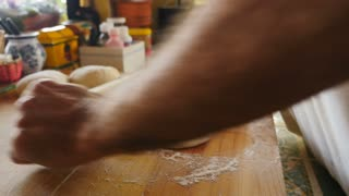 Hand held close up of a man rolling out pizza dough on a wooden cutting board in a home gourmet kitchen