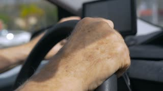 Hand held close up of hands on a steering wheel, driving, while operating a GPS in a car during the day