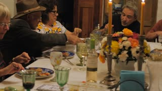 Hand held of a group of people enjoying their dinner at a celebration such as a dinner party, family event, religious ceremony, or passover seder.