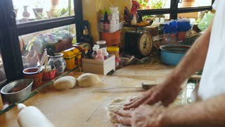 Hand held of an active senior male making pizza dough with his hands and a a rolling pin on a wooden cutting board in his kitchen
