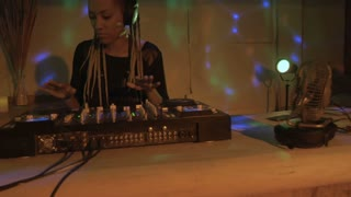 Hand held of an African American woman DJ mixing music in an underground club