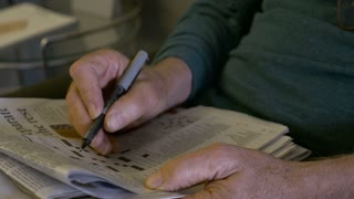 Hand held of an elderly man filling out a crossword puzzle with a pen from a newspaper