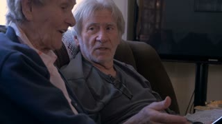 Hand held of an elderly son in his 70s and his older mother in her 90s laughing, talking, and looking at a mobile tablet on a couch in 4k