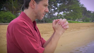Hand held push in shot of a praying middle aged man in a red shirt with hands intertwined together standing on the beach asking for forgiveness in a beautiful tropical setting.