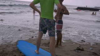 Hand held shot of a beginner surf lesson in Bali with a middle aged caucasian man and Balinese surfing instructor.