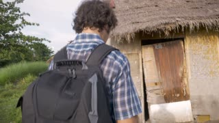 Hand held shot of a confused tourist holding a reservation approaching an abandoned rental as he knocks on the door.