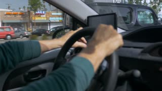 Hand held shot of a man driving a car with both hands on the steering wheel and operating a GPS during the day.
