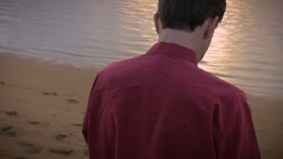 Hand held shot of a middle aged caucasian man in red swiping and checking his cell phone while on the beach during his vacation at sunrise or sunset.