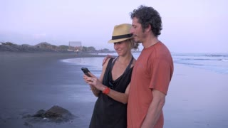 Hand held shot of an attractive, athletic couple sharing a moment together with their phone on the beach. The middle aged man has embraced her phubbing behavior.