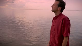 Hand held shot of middle aged man in red shirt closing his eyes, putting his hands together in prayer, looking up to the sky while standing in a calm lake or ocean.
