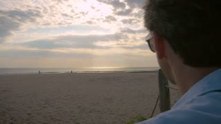 Hand held slow motion shot of two men talking while watching the sunset over the ocean at the beach.