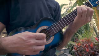 Handheld low angle shot of a middle aged man playing a blue ukulele in the jungle or forest surrounded by tropical plants in paradise.
