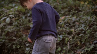 Handheld shot of little toddlers feet and legs in baggy pants walking in grass in slow motion with his father watching over him. There are fallen leaves in the grass at the early stages of autumn or fall.