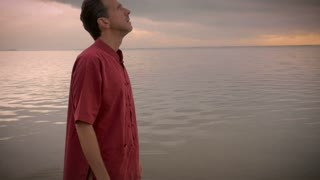 Handheld shot of man in a red shirt standing in a calm ocean starts praying in deep thought and looking up at the sky for answers as the sun rises and the camera follows him in an arch shot from side to side.