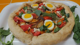 Healthy, home cooked vegetarian pie with hard boiled eggs, cheese, tomatoes, onions, spinach, and rosemary push in dolly shot