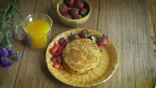 High angle dolly shot of healthy organic breakfast of fresh strawberries, home-made pancakes, and fresh squeezed orange juice with purple flowers and babies breath garnish on a rustic wooden table.