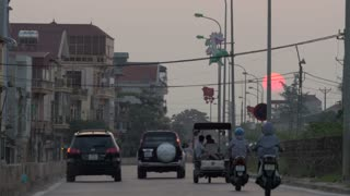 Large orange red sun sets slowly in background while cars and scooters move towards the sunset - returning home after a full day of work against an urban backdrop of Hanoi, Vietnam