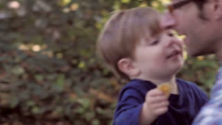 Little blond boy having fun and hugging his 30 something father outside in green yard with soft focus.